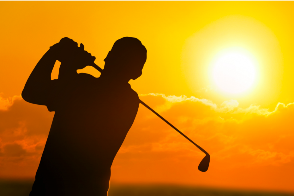 man golfing in sunset
