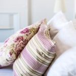 purple stripy pillows on white bed